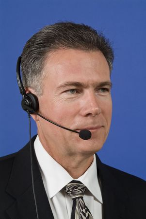 helpdesk: A man wearing a headset as if manning a helpdesk or providing telecommunication of some sort.