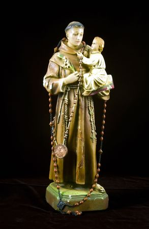 An antinque statuette of Saint Joseph holding  Jesus isolated on black.