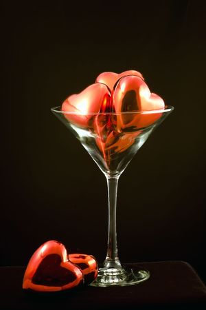Martini glass filled with shinny red hearts isolated on a black background.