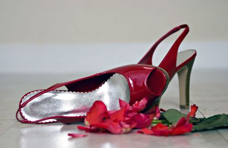 Red high-healed shoes left on the floor next to a crushed rose implying an evening that ended in disappointment