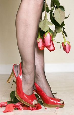 ankles sexy: A woman in bright red patent leather shoes crushing roses portraying unforgiveness and anger.