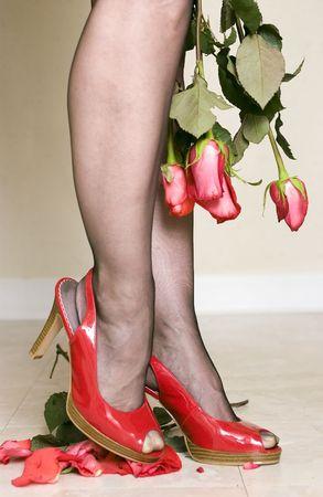 pigiatura: Una donna in pelle verniciata rossa luminosa calza schiacciare le rose che ritraggono il unforgiveness e la rabbia. Archivio Fotografico