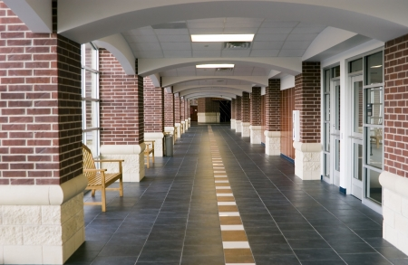 hallway: Bright sunlight pours in on the brick pillars that line the empty hall of a very large high school building.