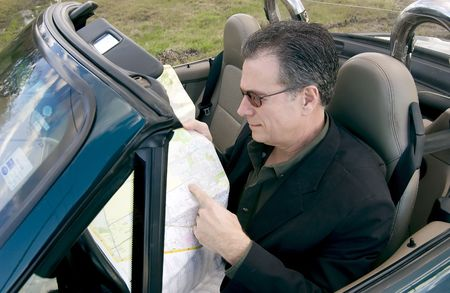 Man sitting in a convertible pointing at a place on a map indicating his destination.
