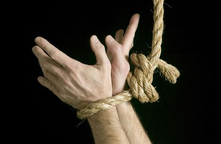 Hands of a caucasian male tied together with a long rope with fingers spread wide as if struggling to get free.