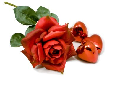 Red rose isolated on white with three little shinny red heart shaped ornaments lying along side it.  photo