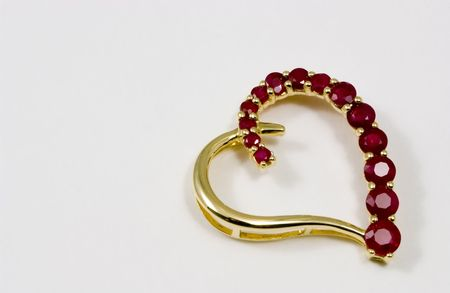 Gold heart shaped pendant with little rubies forming one side of the heart.  photo
