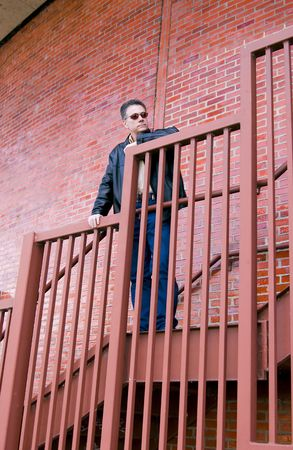 observe: Man in a pensive mode standing on the steep stair case of a large circular red brick building.