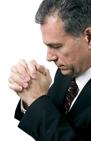Man with hands folded and head bowed in a posture of prayer.