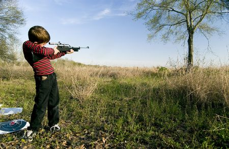 carefully: Young boy with his pellet gun carefully looking through the scope aiming at a distante tree on a beautiful sunny day. Stock Photo