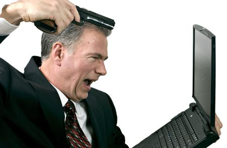 illogical: Man furious with his bad stock trades taking it out on his computer by shooting at it. Stock Photo