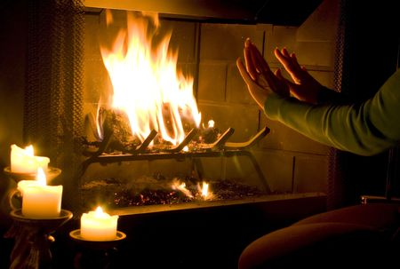 A woman warming her hands by a roaring fire with  candles lit to add to the ambiance.