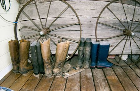 A row of work boots lined up in front of decorative wagon wheels, ready and waiting for use on the ranch.