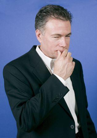 determining: El hombre negro en un negocio conjunto con su mano hasta su boca y una expresi�n en su rostro como si se trata de una cuesti�n delicada o situaci�n.  Foto de archivo
