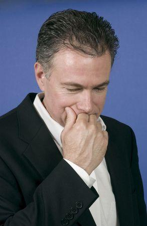 determining: Var�n maduro, hermoso, blanco en un juego de negocio negro y una camisa blanca con su mano hasta su boca como si se ocupe de una cierta clase de dilema. Foto de archivo