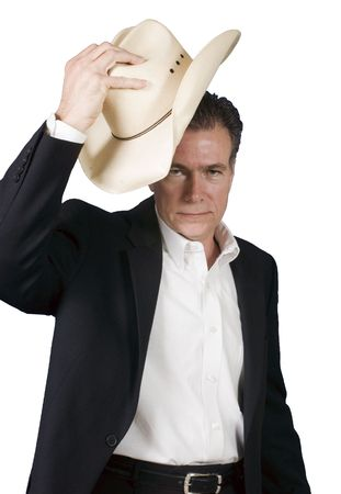 suite: Mature, handsome, white male wearing a black suite and a white shirt holding a cowboy hat with one hand as tipping it in a polite greeting.