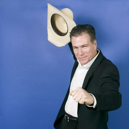 suite: Mature, handsome, white male wearing a black suite and a white shirt holding a cowboy hat with one hand as if in celebration or exhilaration. Stock Photo