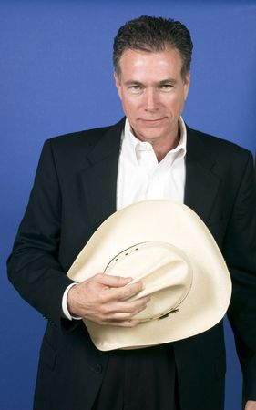 courteous: Mature, handsome, white male wearing a black suite and a white shirt holding a cowboy hat with one hand.