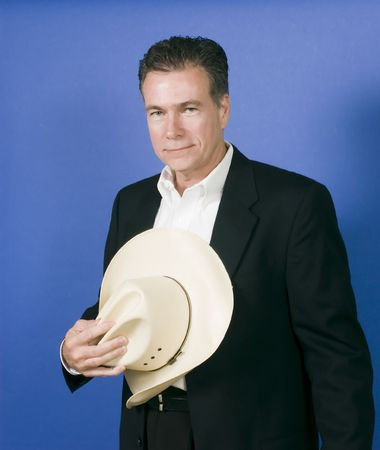 suite: Mature, handsome, white male wearing a black suite and a white shirt holding a cowboy hat with one hand. Stock Photo