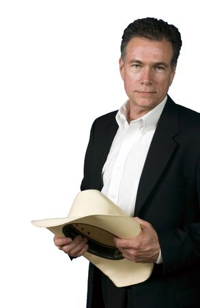 suite: Mature, handsome, white male wearing a black suite and a white shirt with a cowboy hat held in his hands.  Stock Photo