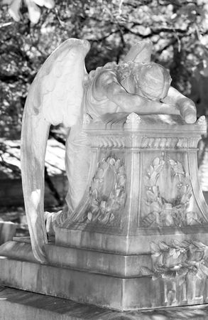Cemetery angel bowed in a sorrowful pose Stock Photo