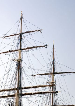 furled: The masts of a vintage sailing vessels with its sails furled and its rigging at rest.  Stock Photo