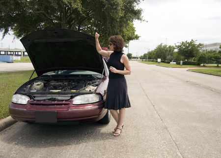 apparently: A woman standing next to a vehicle apparently experiencing car trouble.