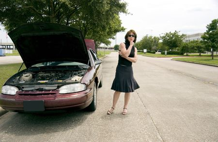 A woman, with apparent car trouble, looking anxiously off into the distance. 版權商用圖片