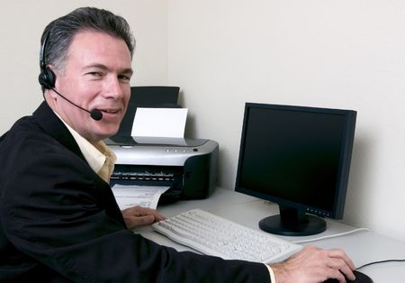appears: Man sitting at what appears to be a helpdesk with a happy expression on his face.  Stock Photo