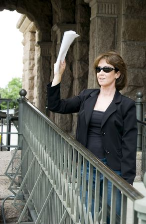 motioning: Woman standing on a ramp leading to a large stone building motioning to someone with sheets of paper in her hand.  Stock Photo