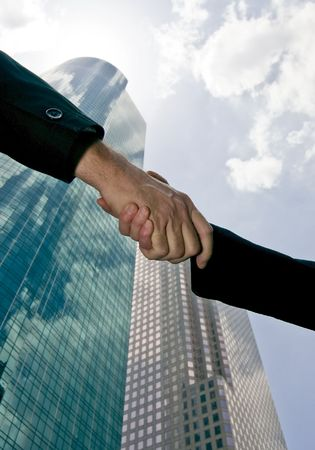 A handshake taken against a sky with tall beautiful glass towers of commerce filling the background