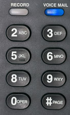 A macro shot of a desk phones voice mail alert button and number buttons.