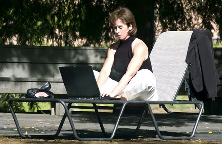 composing: A woman sitting in a lawn chair, working on a laptop computer, and enjoying the beauty of wireless technology.