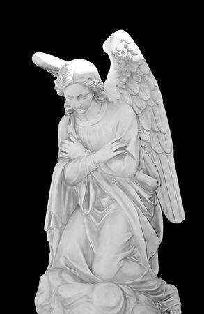humility: Bella scultura in marmo di un angelo in ginocchio isolato su sfondo nero.  Archivio Fotografico