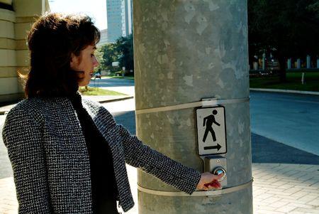 Atractive woman pressing crosswalk button at intersection Фото со стока