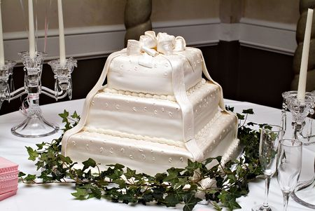 White wedding cake on a tabel with candles photo