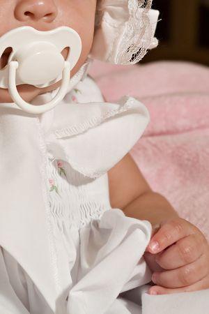 아기 소녀 노리개에 젖꼭지를 빠는에 앉아. 스톡 콘텐츠