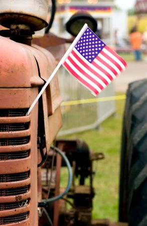 Antique tractor with American flag attached to grill