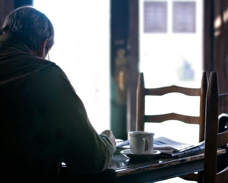 Man relaxing , reading the morning paper with a cup of coffee photo