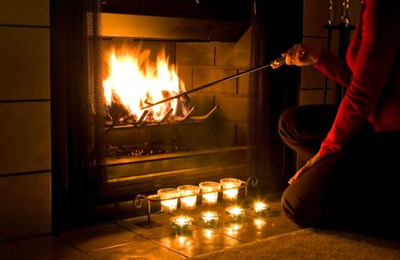 Woman in red sweater stoking a fire in the fireplace with candles burning in front