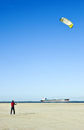 flying man: Man on the beach flying a large kite.