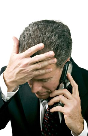 reacting: Businessman on a cell phone reacting in a distressed manner to what is being said during a phone conversation.