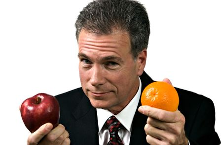 Businessman impressing upon his group the fallacy of using unlike measures.  Stock Photo