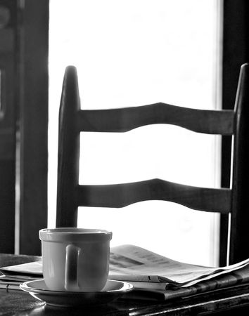 Coffee cup and newspaper on a table with a chair in background in front of a window using natural light photo