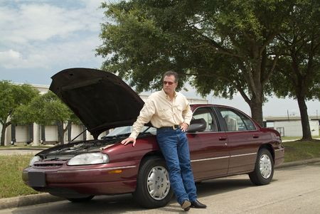 An annoyed man, who is apparently experiencing car trouble, waiting for a tow truck or assistance of some sort.