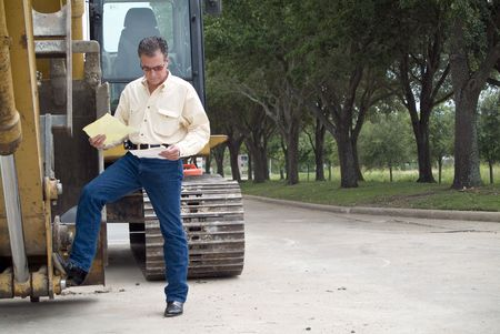 idle: A man standing with his foot on the bucket of an idle backhoe with documents in his hand.