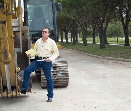 A man standing with his foot on the bucket of an idle backhoe with documents in his hand.