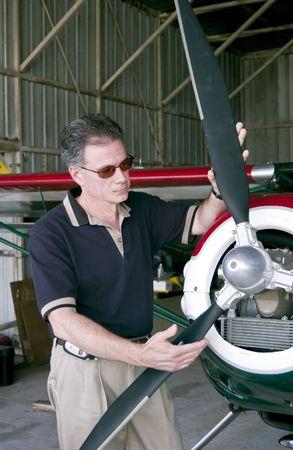 Een man staat met zijn handen op de propeller van een kleine eenmotorige vliegtuig.