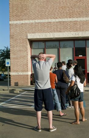 A line of people waiting in front of a building waiting for the business to open.  Stock Photo