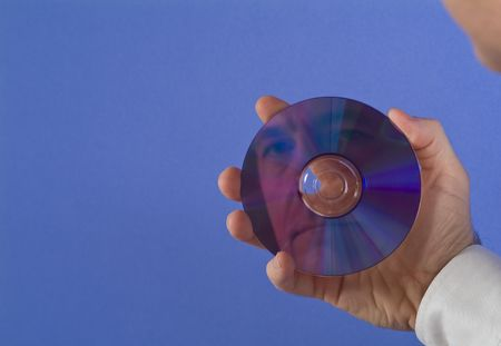 transcribe: A man holding a DVD or CD with his face reflecting back at him with available copy space.